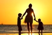 9087497-mother-and-two-kids-silhouettes-on-beach-at-sunset